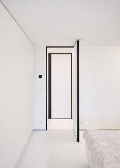 Moderne witte binnendeur met een zwarte omlijsting en verticaal ingebouwde handgreep.