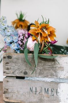 | SPRING TROPICAL WEDDING | Natural, gathered from the garden look bridesmaid's bouquets in a rustic crate , made with bright flowers poppies, garden roses, anemones, fritillaria, scabious, delphiniums, lilac & eucalyptus for their beautiful wedding at Polhawn Fort on the coast of Cornwall.