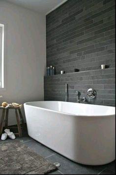 modern bathroom with soaking tub + grey tile + tiled shelf