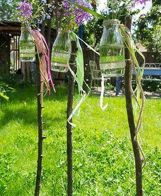 """Festlich und originell für die Grillparty: Blumenvasen aus kleinen Glasfläschchen markieren an Stöcke gebunden die """"Partyzone"""" im Garten und sind gleichzei..."""