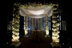 Wedding chuppah in white wrapped in rich flowers with draping and uplighting. By Diana Gould Ltd.