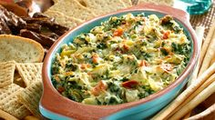 You're looking for a real crowd pleaser, and we've got the solution - Hot Spinach & Artichoke Dip! You'll love how easy it is to make, and your friends will love the to-die-for taste. Preheat oven to 350°. Combine all ingredients except 1/2 cup cheese. Spoon into a 2-quart casserole, then top with remaining 1/2 cup of cheese. Bake for 35 minutes or until dip is hot.