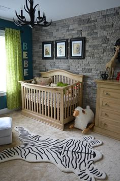 "This stone accent wall gives this ""Wild Kingdown"" nursery a rustic, yet upscale look! #nursery"