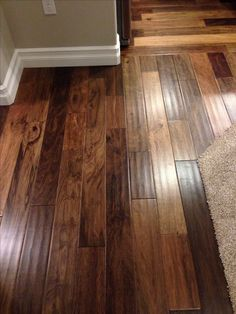 African ebony engineered wood floor by Mohawk. 5 inch plank, hand scraped. Would look good with black, white, or any color of wood cabinets because of the diverse colors.