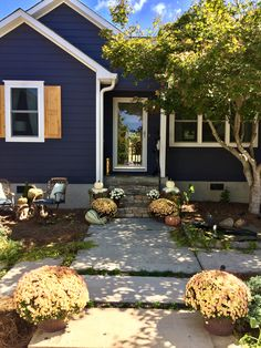 Charcoal blue by sherwin Williams exterior is a beautiful navy. Fall decor and cedar DIY shutters for the curb appeal. Home makeover for the win!