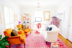 A vibrant and bright home office with orange armchairs, white sofa, pink rug, white bookshelf, and clothing rack