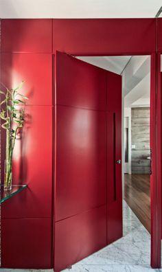 Na entrada do apartamento dos arquitetos Rodrigo Costa e Alessandra Marques, de São Paulo, a porta (2,10 x 1 m, R$ 4 850, Mazu-sil Marcenaria)e o painel de MDF de laca vermelha parecem uma peça única. Uma cava discreta serve de puxador.