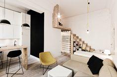 """O apartamento com 29 m² na Polônia, era mais alto do que amplo: com pé-direito de 3,7 m, o jeito foi elevar o dormitório para um semi-mezanino, 1,85 m acima de um corredor com banheiro e guarda-roupas. Nesse """"quarto"""", a altura é de apenas 1,35 m. Ao descascar a parede que dá base às escadas, os arquitetos do escritório 3XA descobriram tijolos muito antigos e danificados, que tiveram de ser pintados de branco. O edifício foi construído há mais de um século"""