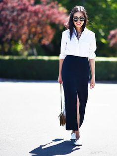 Ash Sundstrom wears a white button-down top, slit black skirt, white flats, and a shoulder bag.