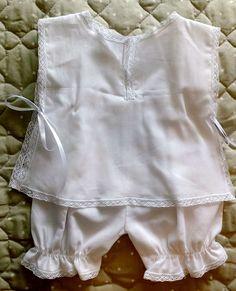 Ref.: BSR2  Lindíssimo Banho de Sol em tecido100% algodão.  Blusinha: rendinhas e bordado inglês na frente; Costas em cambraia de algodão,com fecho em fitinha de cetim. Rendinhas de algodão.  Calça curta em cambraia e rendinhas de algodão.  Tamanho: RN, veste bebê de 0 a 3 meses.