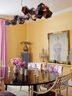 Bright mango orange walls pair beautifully with violet curtains and pink and white ikat print dining chairs for a dining room that's bursting with personality.