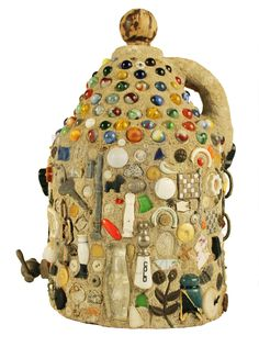 This memory jug was constructed by putting various objects on a jug encased in concrete. Some identifiable objects include marbles, a spigot, a saltshaker, a penny, a metal chain, pins, keys, buttons, ceramic, porcelain, glass decorative objects, and a small metal.