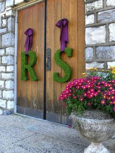 Inicjały na drzwi wykonane z mchu jako dekoracja ślubna