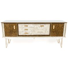 A British 1960s faux wood sideboard refurbished and embellished with white laminate facings by Reload craftsmen. New hair pin legs have been added and finished in gold to match cabinet fittings. All drawers have been re-seated and made good. The piece is unique and will not be repeated in these finishes.  https://www.1stdibs.com/furniture/storage-case-pieces/credenzas/british-mid-1960s-faux-wood-sideboard/id-f_2315423/
