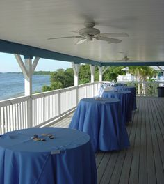 Tables covered by blue linens on the outdoor balcony overlooking the water at the Tampa Bay Watch in St. Petersburg, Florida