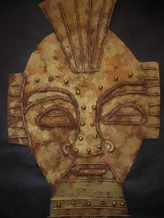 African Masks using yarn, noodles, and beads then dabbed with gold and bronze paint