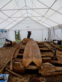 The underside of the 2 curved bottom planks (producing the rocker in the boat), and a side plank, of the half-scale reproduction of the Dover Bronze-Age boat, Dover 2012. The v-shaped gap at this end is where the bow piece of the boat will be fitted. Trevor Marsden is taking a photo, photo © Rachel Head.