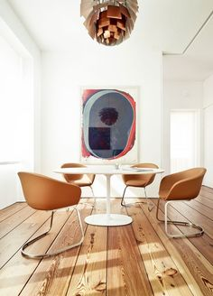 Dining room with wooden floors and statement art.