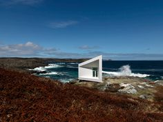 Saunders architecture: squish studio along the coastline of Fogo island in newfoundland, Canada. The 30 square meter building is perched upon the rocky terrain and supported with a system of stilts.