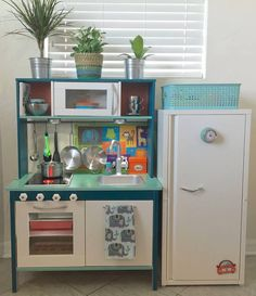 DIY PLAY KITCHEN    IKEA Hack  + DUKTIG play kitchen  + JOSEF cabinet       Custom-Painted & Designed   + Montana Gold spray paint + Rejuvenation hardware  * Gender-Neutral * Natural Wood with Teal, Mint, White, & Silver * LED Lights (under cabinet/in oven)