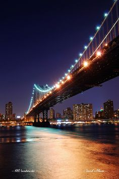 New York City Manhattan Bridge over Hudson River with skyline after sunset night view illuminated with lights viewed from Brooklyn. NYC.