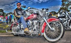 Classic American red Harley Davidson Heritage Softtail with male owner at car…