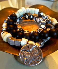 Black and white agate, bone, and pyrite with double sided charm...butterfly/believe. From August Heart.  Pricing/purchasing information, contact: Jamie Lewis  jamielewisandco@gmail. com  Facebook.com/augustheart