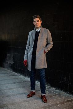 Men's grey wool coat, red leather gloves, white shirt with grey dots, black v-neck jumper, blue jeans, white socks with horizontal grey stripes and brown leather shoes. Can't get better than that!