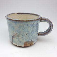 A handmade ceramic mug with light blue glaze and hand drawn house and tree print. It was thrown and hand modelled with red clay in my studio
