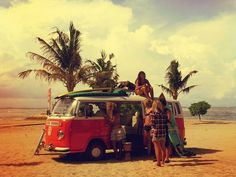 Surf hippie girls with surfboards on Volkswagen van at beach ...