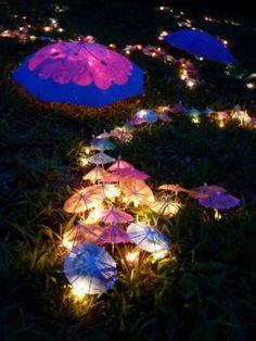 Guarda-chuvinhas iluminando o jardim para uma Festa Fada! Use luzinhas de árvore de Natal e mini guarda-chuvas para reproduzir. Fofo demais!