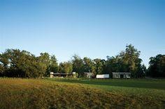 La casa principal con una galería paralela a la pileta, amplio living-comedor y dormitorio en suite es el corazón de esta pequeña aldea que completan dos cabañas y dos carpas. El invernadero, donde se cultivan los almácigos para plantar en todo el jardín, está en el centro del terreno