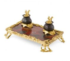 LOUIS XV STYLE LACQUER AND GILT BRONZE MOUNTED INKSTAND LATE 19TH CENTURY the shaped rectangular stand decorated with fishermen and trees, surmounted by two inkwells modelled as tied sacks and with squirrel finials, raised on openwork bracket feet 31cm wide.