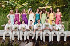 Each girl with a different color dress. Bridesmaids bouquets are white daisies and bride's is multicolor wildflowers