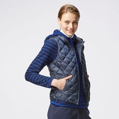 This warm down vest is thin and lightweight. A densely woven shell and water-repellent thread keep out moisture. The quilted diamond pattern gradually shrinks toward the waist for a slender appearance, and the matte finish provides an elegant look. The high collar provides a snug fit to keep out cold wind, and the armholes are reinforced with attractive binding. This vest folds to a compact size so you can easily carry it in its attached pouch.