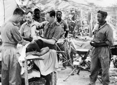 Doctors tend a wounded soldier of the 81st West African Division in an improvised operating theatre in the Kaladan Valley, Burma.