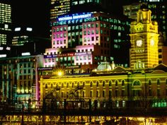 Flinders St. Station illuminated at night.  Picture taken from Yarra River bank Photography by Holger Leue