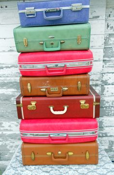 stack of colorful vintage luggage...I think I own every one of these!