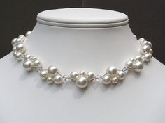 This necklace is made with beautiful 10mm, 8mm, and 6mm round Swarovski white pearls as well as 6mm Swarovski clear crystal bicone shaped beads. The necklace is approximately 17 inches in length. The clasp is a sterling silver lobster claw clasp. All findings are made of sterling silver. The necklace can be worn with the large pearls laying in opposite directions, the same direction or however they lay.    Matching items…