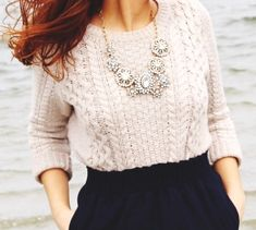 Beige sweater + black skater skirt. Big jewelry accent.