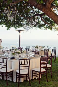 Love this outdoor setting and the crystal chandeliers in the tree...awesome!