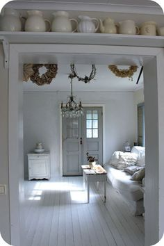 White painted floors, white furniture and gray door.