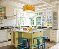 Fresh, lemony green paint creates a lively atmosphere in this sunny kitchen. White cabinetry and tiles allow the bright island to shine, and turquoise stools offset the citrus hue with another pop of bright color! http://www.bhg.com/kitchen/island/colorful-kitchen-islands/?socsrc=bhgpin031915citrusblisskitchen&page=2