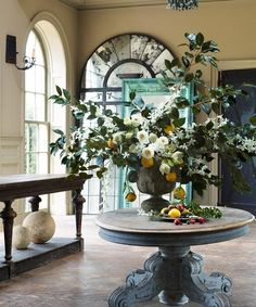 Round table with huge floral center piece and drapers table open storage