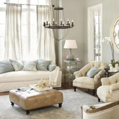 stylish-neutral-living-room-designs-Chandelier-candle-design-single-sofa-white-carpet-pouffe-cushion-curtain-lamp-table