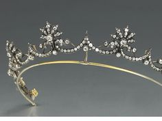 An antique diamond and silver topped gold tiara, circa 1880 designed as an old European and old mine-cut diamond garland surmounted by six ...