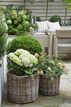 maceteros grandes, decoración de jardín con flores en macetas de canastas tejidas, mesa y sillas de rattan, plantas verdes