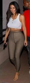 Kim, 38, wore her usual flesh-baring fashion, going braless in a white cropped top that exposed a hint of underboob and a pair of taupe-colored skintight leggings for the cinema trip.