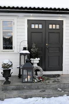 Julen ønskes velkommen allerede ved inngangsdøren. To store lykter med tente kubbelys, og et minitre møter deg på trappen. Beboerne har også valgt å legge dørkransen på bakken ved lyktene.Klikk