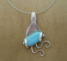 "This unique pendant is made from an antique silver plated fork and is adorned with a turquoise stone. The fork tines are bent around the stone to create a wearable ""piece of art!""    This fabulous pendant measures 2 3/4 inches long (from the top of the bail to the bottom of the pendant) and 1 3/4 inches at its widest point.     Included with this pendant is a 17 ½ inch wire choker, but it can easily slide on to another chain."